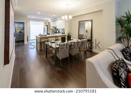 Nicely decorated dining table and the kitchen at the back. Interior design.