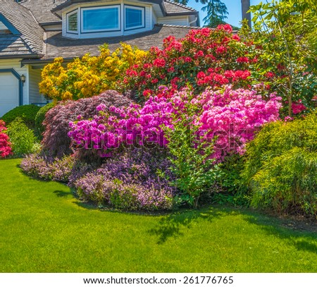 Nicely decorated front yard with flowers, stones and bushes as a decorative elements. Landscape design.