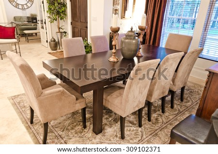 Nicely decorated luxury living, dining suite: dining room with the table and some chairs and and the lobby at the back. Interior design. - stock photo