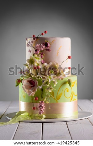Nicely decorated wedding cake made of two levels of different sizes served on a tray. Various kinds of flowers as a decoration. Accurate work of the baker in special lighting. Lovely ribbon below. - stock photo