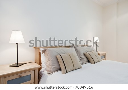 nicely done double bed with beige sheets - stock photo