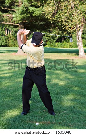 Nicely dressed golfer - back swing on the fairway. - stock photo
