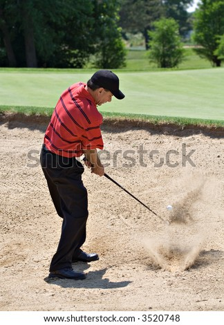 Nicely dressed professional looking male golfer hitting out of sand trap. - stock photo
