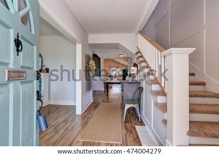 Nicely furnished hallway interior with vintage cabinet and white railings staircase. Northwest, USA