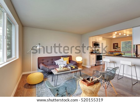 Nicely furnished living room interior after remodeling with wicker details in decor. The room is adjacent to the kitchen. Northwest, USA