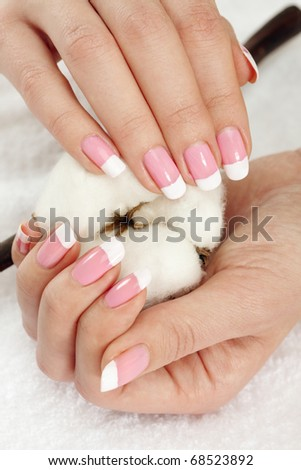 Nicely manicured hands with cotton crop over a towel - stock photo