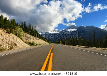 Nicely paved road into the mountains.  Conceptual idea for taking the high road or taking the road to the top.