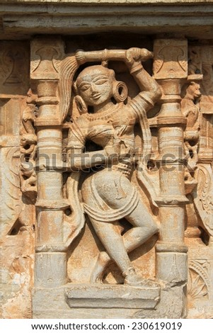 Nicely poised sculpture of maid servant on wall pane at Vijay Sthambh (Victory Tower), Chittorgarh Fort, Rajasthan, India, Asia