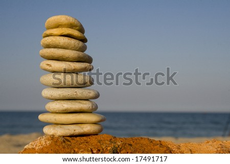 Nicely stacked tower of rocks on beach - stock photo