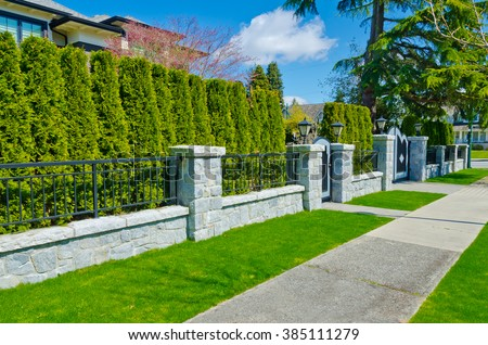 Nicely trimmed and landscaped bushes, green fence and front yard behind pedestrian sidewalk on empty street. Landscape design. - stock photo