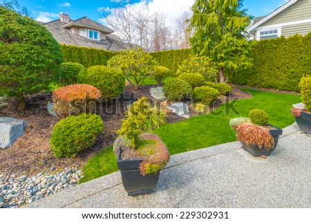 Nicely trimmed and landscaped front, back yard. Flowers and stones in front of the house, front yard. Landscape design. - stock photo