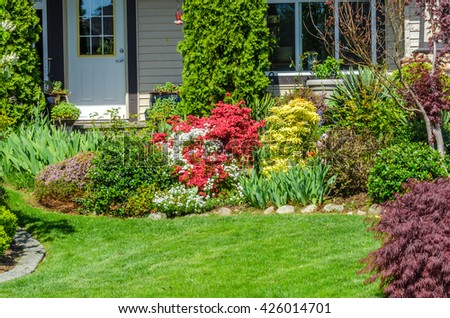 Nicely trimmed lawn and flowers and stones in front of the house, front yard. Landscape design.