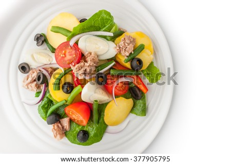 Nicoise salad on the white ceramic plate top view