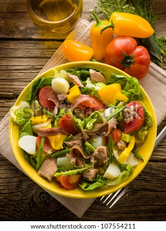 nicoise salad over wood background - stock photo