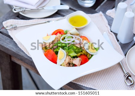 Nicoise Salad with canned tuna, anchovies, hard boiled eggs, tomatoes, olives, onions, lettuce, and green beans. French cuisine - stock photo