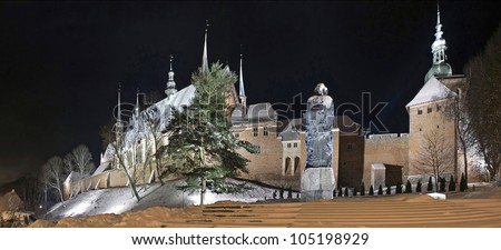 Nicolaus Copernicus Monument in the background of the cathedral in Frombork, a place where he worked Copernicus. Illumination, winter. - stock photo