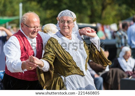 NIEUWEHORNE, THE NETHERLANDS - SEP 27: Elderly man and woman demonstrating an old Dutch folk dance during the agricultural festival Flaeijel on September 27, 2014, the Netherlands