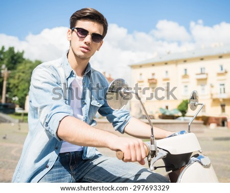 Nifty young man in sunglasses riding scooter on sunny day. - stock photo
