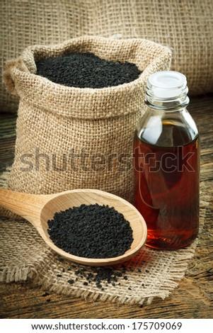Nigella sativa (Black cumin) on wooden spoon and essential oil - stock photo