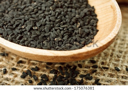 Nigella sativa (Black cumin) on wooden spoon. Macro shot - stock photo