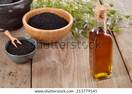 Nigella sativa oil in a bottle and nigella seeds and flowers on wooden background. Black cumin healing herb. Cold pressed, non refined oil. Traditional medicine. - stock photo