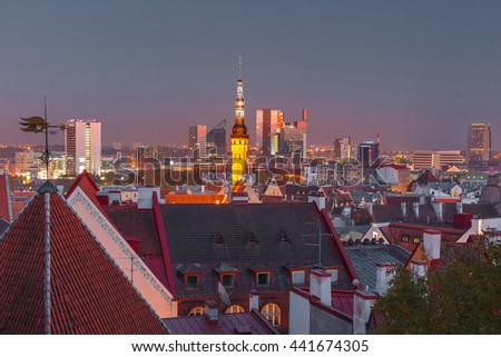 Night aerial cityscape with old town hall spire and modern office buildings skyscrapers in the background in Tallinn, Estonia - stock photo