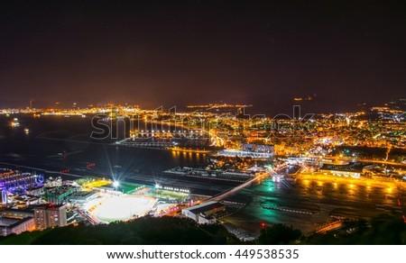night aerial view of illuminated gibraltar, its airport, la linea de la concepcion town in spain and algeciras bay. - stock photo