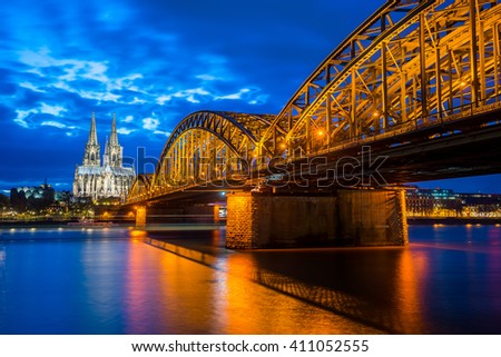 Night at the Cologne Cathedral with Hohenzollern Bridge in Cologne, Germany.