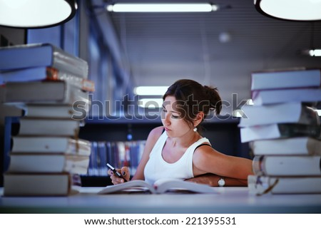 Night before finally exam, female student studying in library, asian college student seated at the desk with stack of books, female college student surrounded by books in a library - stock photo