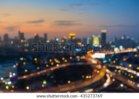 Night blurred light highway overpass with city downtown sunset sky background - stock photo