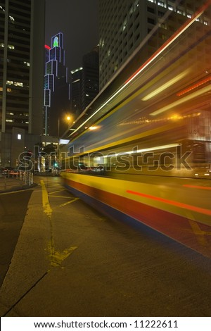 Night bus lit by advertisement lights on Hong-Kong street