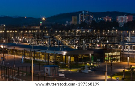 Night city Adler on the Black sea In the foreground train station , next town , on the background of the snow-capped Caucasian mountains