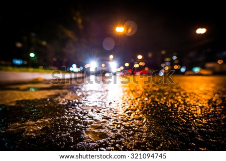 Night city after rain, approaching car headlights shine. View from a wide angle at the level of the asphalt - stock photo