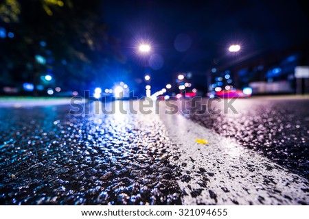 Night city after rain, approaching car headlights shine. View from the level of the dividing line, in blue tones - stock photo