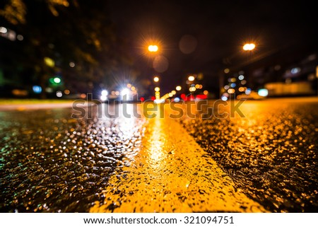 Night city after rain, approaching car headlights shine. View from the level of the dividing line - stock photo
