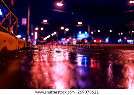 Night city after rain, night view of the busy highway from the curb at the asphalt level. Image in the blue-purple toning - stock photo