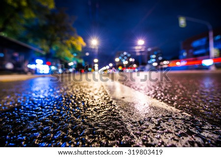 Night city after rain, the glowing lights of approaching cars. View from a wide angle at the level of the dividing line, in blue tones - stock photo