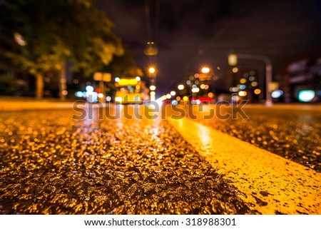 Night city after rain, the glowing lights of approaching cars. View from the level of the dividing line - stock photo
