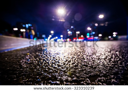 Night city after rain, the glowing lights of approaching cars. View from the side of the road at the level of the asphalt, in blue tones - stock photo