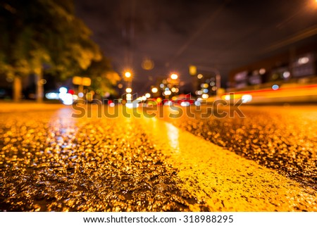 Night city after rain, the headlights of passing cars racing. View from the level of the dividing line - stock photo