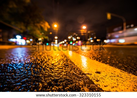 Night city after rain, the headlights of passing cars racing. Wide angle view of the level of the dividing line - stock photo