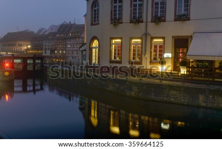 Night city along the river lit by night lights Lantern in the fog, in the buildings in the windows of the light is - stock photo