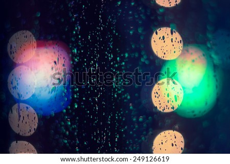 night city life through windowpane: darkness and rain - stock photo