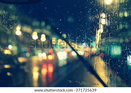 night city life through windshield: cars, lights and rain, vintage style photography - stock photo
