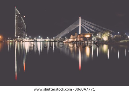 night city reflections in river, Riga, Latvia - vintage effect