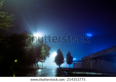 Night city street covered with fog, blurred city lights glow through misty haze, a neon sign glows afar - stock photo