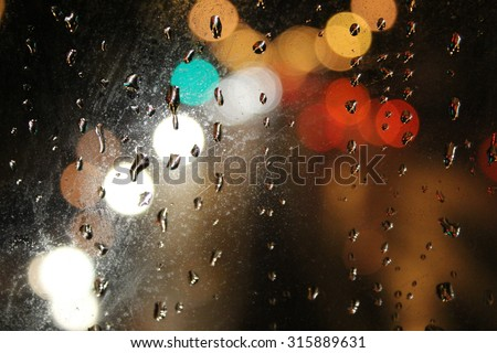 Night city through wet window. Raindrops on the glass, on a background of the night city. - stock photo