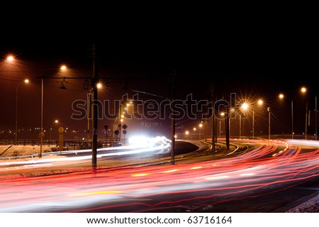 night city traffic lights in motion under street lamps - stock photo