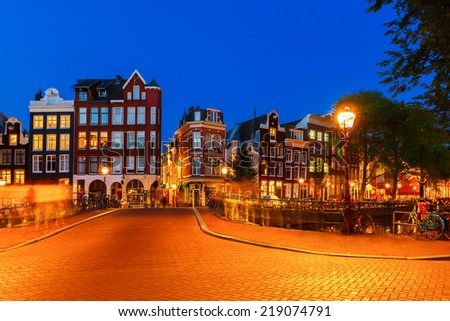 Night city view of Amsterdam canal, bridge and typical houses, boats and bicycles, Holland, Netherlands. Long-exposure photography. - stock photo