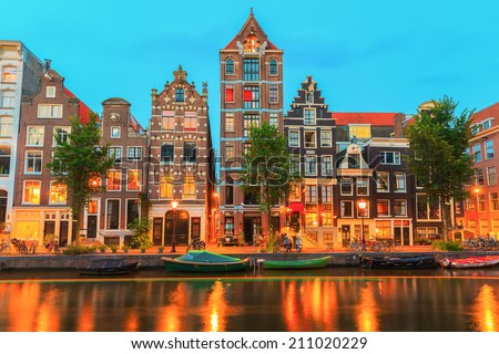 Night city view of Amsterdam canal Herengracht with typical dutch houses, boats and bicycles, Holland, Netherlands. - stock photo